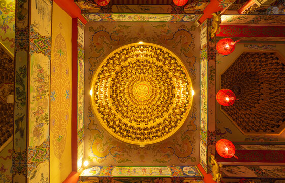 Bottom view of golden chandelier hanging ceiling golden light with red lamp lanterns in Chinese temple. Circle square frame. Decoration painting.