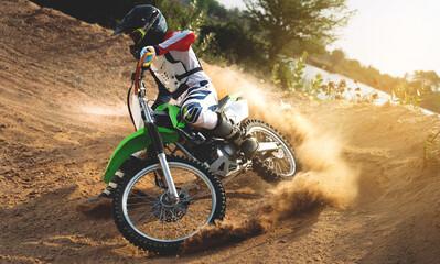 Young man practice riding dirt bike.Splashing sand