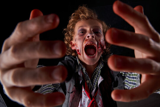 boy disguised as zombie with blood and glitter with hands in front and with expression of fear