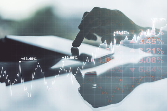 Multi exposure of abstract financial graph and hand working with a digital tablet on background, financial and trading concept