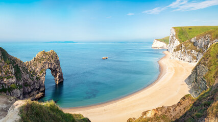 Fototapeta Aerial view of Durdle Door natural formation at UNESCO heritage Jurassic Coast. The Isle of Portland can be seen on the horizon. Copy space in blue sky.
