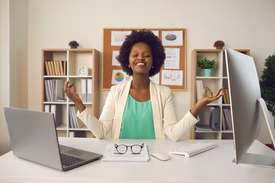 Happy employee getting ready to start productive work day. Young business woman sitting at office desk and meditating eyes closed thinking of good things and focusing on positive feelings and emotions