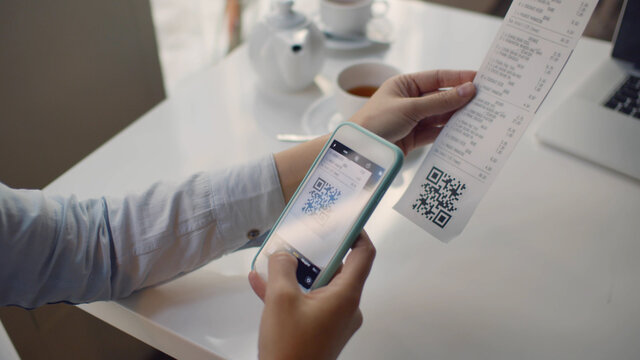 Close up of woman using smartphone and scanning qr code on cash shop receipt