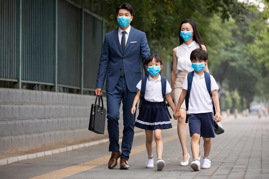 Young family wearing surgical masks and walking outdoors
