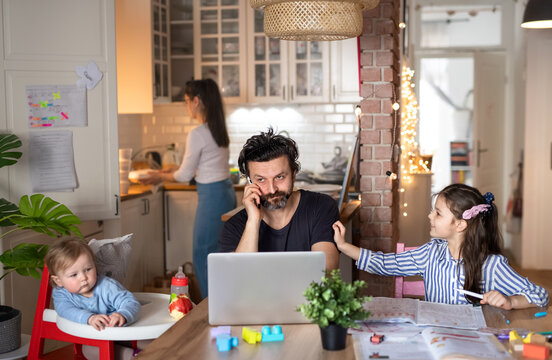 Father with small daughters in kitchen, distance learning, home office and schooling concept.