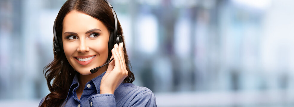 Contact Call Center Service. Customer support, female sales agent. Caller or answering phone operator or businesswoman in headset. Brunette young woman. Blurred modern office interior background,.