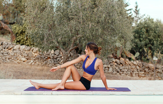 Young woman practicing Sage Marichi Yoga pose in a garden