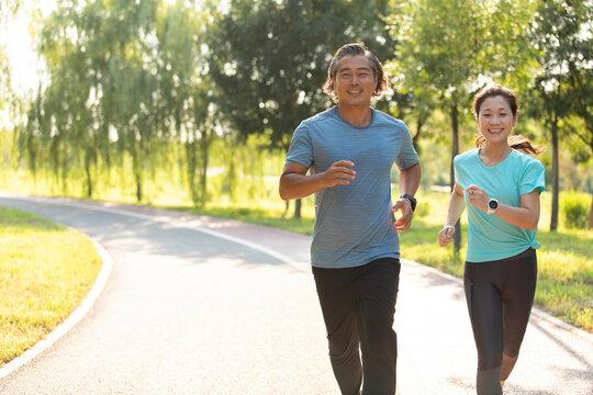Happy mature couple running in park