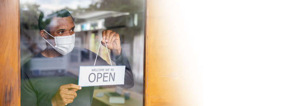 Portrait of African offee shop black man owner with face mask open after lockdown quarantine. Happy guy hang open door sign in coffee shop. Startup small business owner reopen restaurant banner
