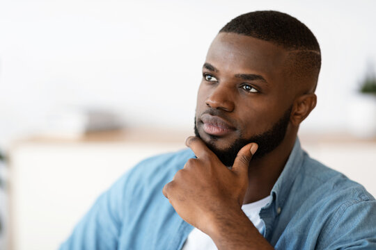 Portrait Of Thoughtful Black Millennial Man Touching Chin And Looking Away
