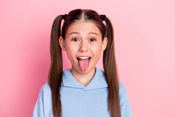 Fototapeta Photo portrait of funky schoolgirl showing tongue fooling playful isolated on pastel pink color background