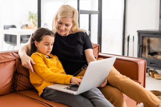 Working from home office with kid. Happy mother and daughter shopping online, using laptop together. Woman hugging child. Freelancer workplace. Female business, virtual communication.