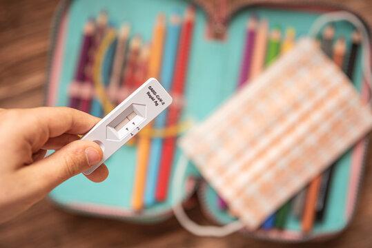 Kind hält negativen Corona-Schnelltest über Schulmäppchen