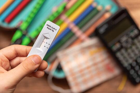 Schulkind hält negativen Corona-Schnelltest über Schulmäppchen