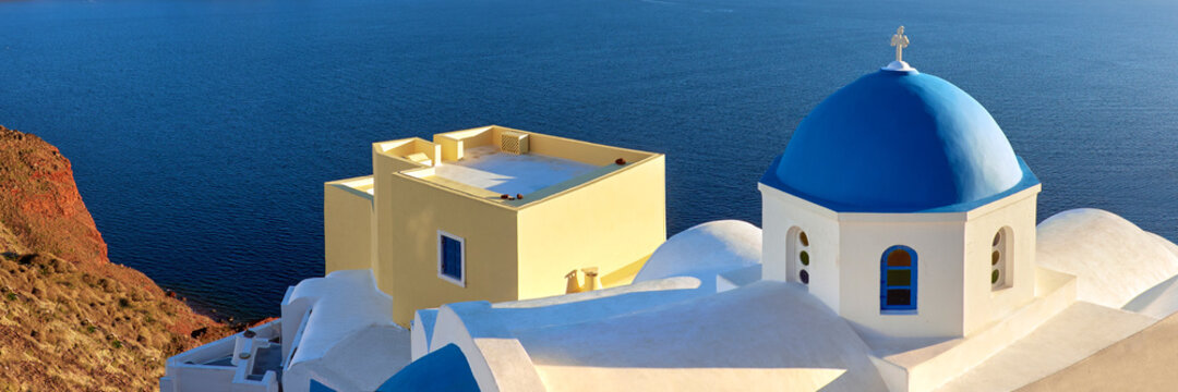 Panoramic image of local church with blue cupola in Oia on Santo