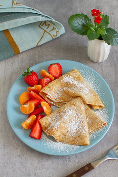 Homemade crepes pancakes served in ceramic plate with strawberries slices and sugar.