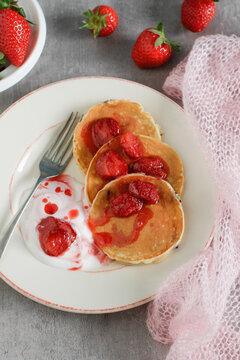 Homemade rustic pancakes stack with strawberry jam and yogurt