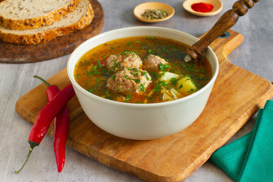 Homemade rustic soup with  meatballs, potatoes and vegetables. selective focus