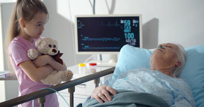 Upset little girl holding teddy bear standing near sick grandmother sleeping in hospital bed