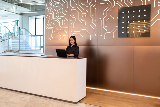 Young businesswoman standing at office reception desk