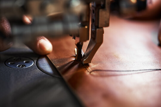 Working process of leather craftsman. Tanner or skinner sews leather on a special sewing machine, close up.worker sewing on the sewing machine