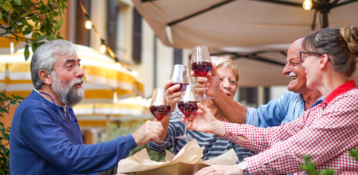 Group of old people eating and drinking outdoor - Senior couples having fun together