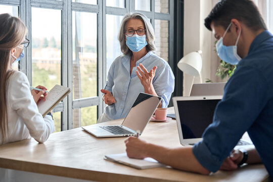 Senior older educator working with computers in office with team wearing medical masks during covid lockdown.Adult experienced business woman is holding meeting with female assistant and male manager.
