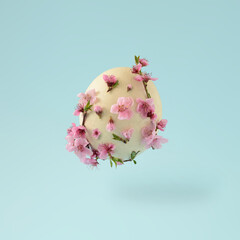 Easter flying ostrich egg with colorful flowers on a bright blue background. Minimal spring concept.