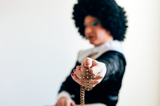 Focus in the foreground on the hand holding a gold crucifix. defocused drag queen disguised as a nun in background. misogyny and homophobia in Catholic culture concept.