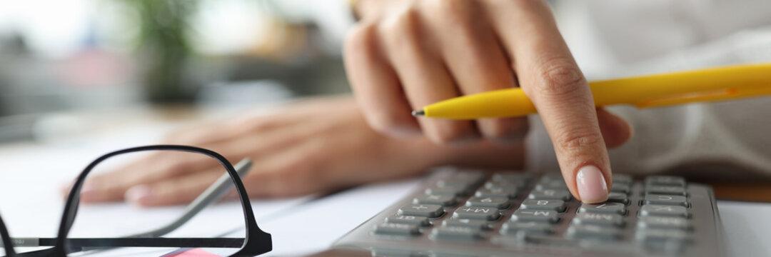 Female finger on a calculator near documents