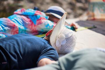 Turyści w kapeluszach słonecznych wygrzewają się na ciepłej plaży w letnie wakacje.