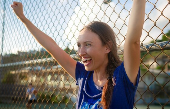 Mother cheering and praising her child at a field game. Happy parents watching kids sports outside.