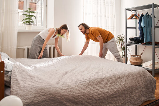 Woman making bed and organizing room in morning with her husband