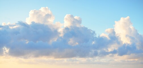 Fototapeta Clear blue sky with glowing pink and golden cumulus clouds after storm at sunset. Dramatic cloudscape. Concept art, meteorology, heaven, hope, peace, graphic resources, picturesque panoramic scenery