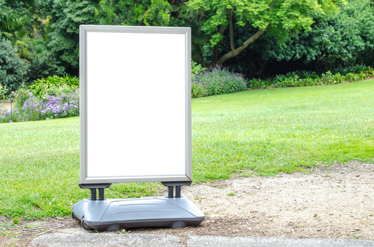 Blank white outdoor advertising stand or sandwich board mockup template. Clear street signage board placed outdoor on the green grass lawn. Background texture of standee in a garden.