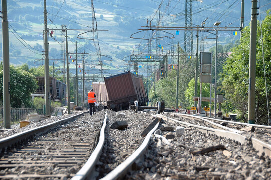 Massive freight train derailed along the tracks. Tracks, freight trolleys, wheels and sleepers damaged after a collision between trains.