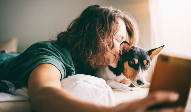 Beautiful young adult woman in pajamas doing selfie with her bassendji dog in morning in bed
