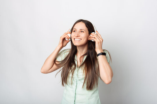 Nice portrait of a woman listening to the music with her new headphones near a white wall