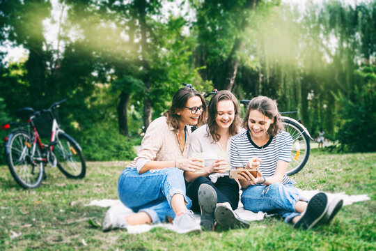 Three young beautiful women friends having fun in a summer park sitting on green grass and looking into a mobile phone