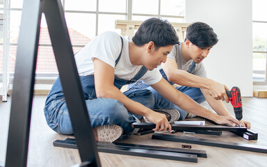Two Asian handsome men wearing blue overalls, helping or supporting each other to assemble make DIY furniture following manual at home. Wall mural