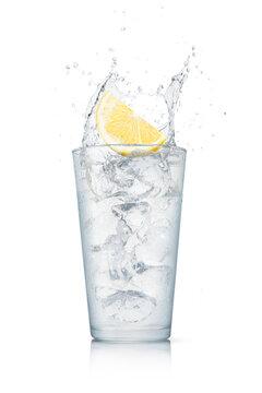 白背景に置かれた氷入りのグラス。落としたレモンで飛沫の上がった瞬間のテクスチャー。レモンサワー、レモンジュース、レモネードなどの素材