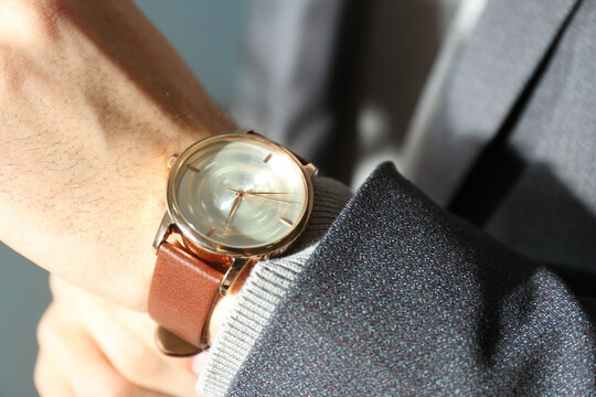 Man with luxury wrist watch on blurred background, closeup