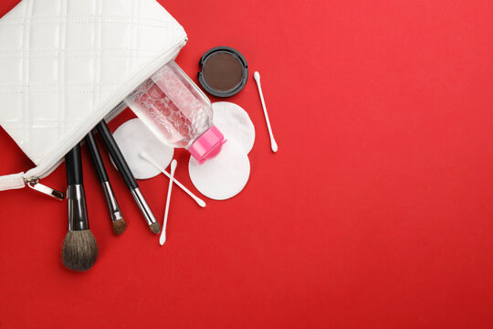 Cotton pads, swabs, brushes and micellar cleansing water on red background, flat lay. Space for text