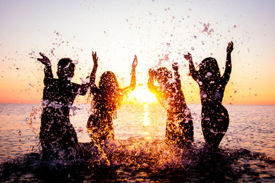 Happy friends splashing inside water on tropical beach at sunset  - Group of young people having fun on summer vacation - People, holidays and summertime concept