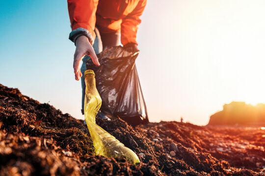 A woman in a jacket, with a garbage bag in her hands, reaches for a bottle to the ground. Bottom view. The sky is in the background. Close up and copy space. Concept of environmental pollution