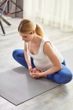 attractive lady in sportswear engaged in workout at home, stretch the body, train body muscles