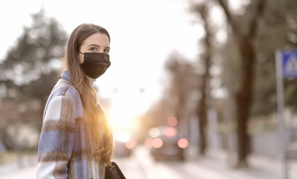 Woman with face mask walking down the street