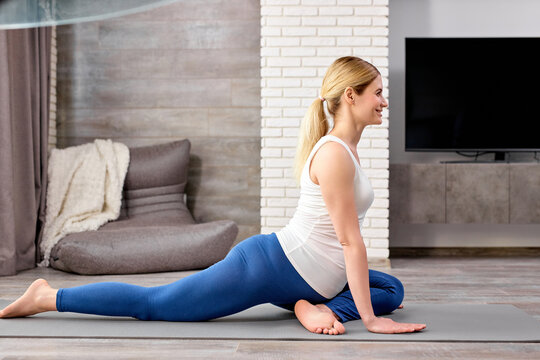 calm future mom-to-be, pregnant female in sportive clothes doing exercises on fitness mat