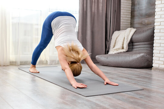 Blonde Female Doing Adho Mukha Svanasana Exercise At Home Alone