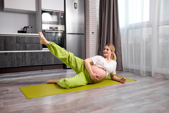 young pregnant woman with naked tummy lifting one leg up, doing exercises on floor